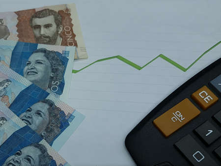colombian banknotes and calculator on background with rising trend green line, view from above