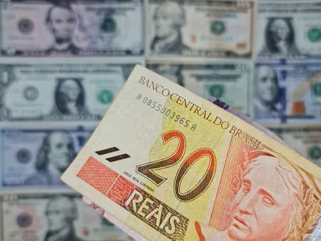 approach to brazilian banknote of twenty reais and background with american dollar bills Foto de archivo