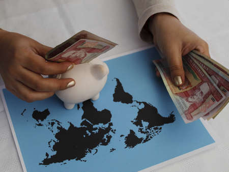 hands of a woman holding guatemalan money with a piggy bank and a world map on the table