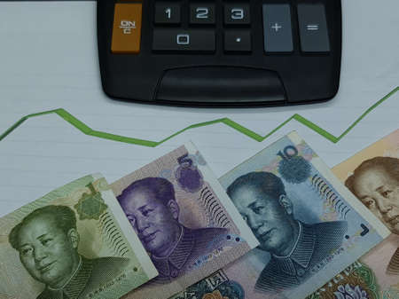 chinese banknotes and calculator on background with rising trend green line, view from above