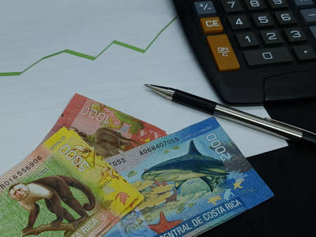 Costa Rica banknotes, pen and calculator on background with rising trend green line