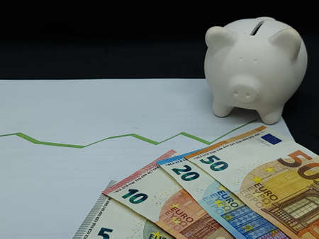 european banknotes and piggy bank on background with rising trend green line Foto de archivo