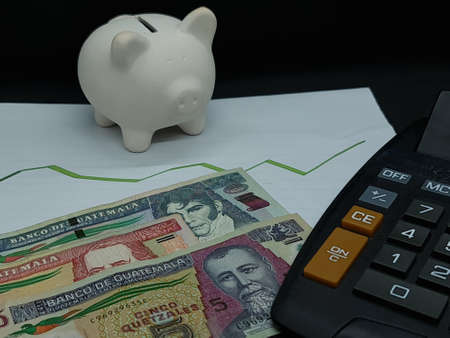 guatemalan banknotes, piggy bank and calculator on background with rising trend green line