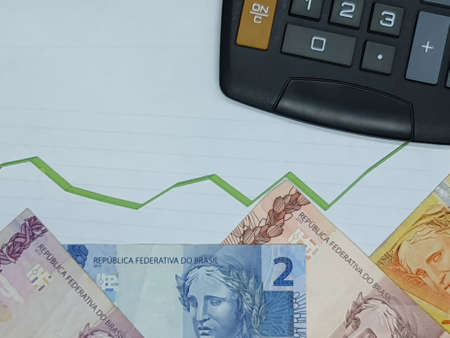 brazilian banknotes and calculator on background with rising trend green line, view from above