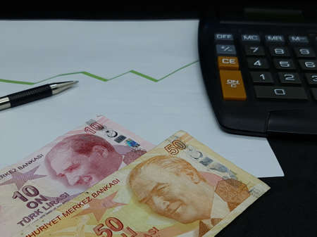 turkish banknotes, pen and calculator on background with rising trend green line