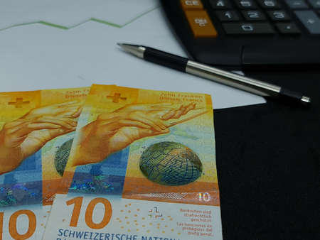 swiss banknotes, pen and calculator on background with rising trend green line