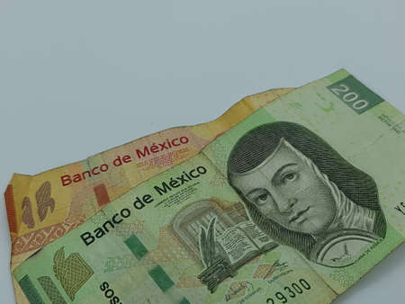 approach to stacked mexican banknotes on the white background