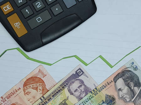 honduran banknotes and calculator on background with rising trend green line, view from above
