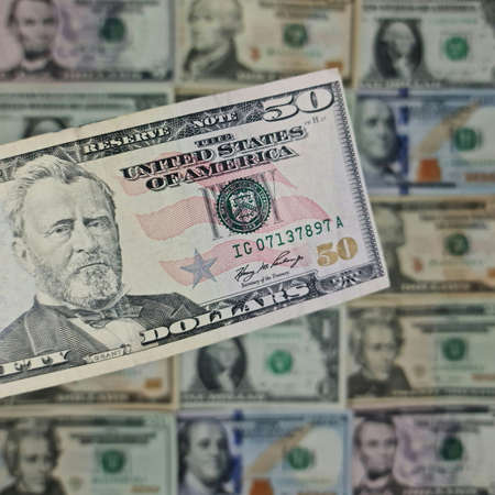 approach to american fifty dollars banknote and background with american dollar bills