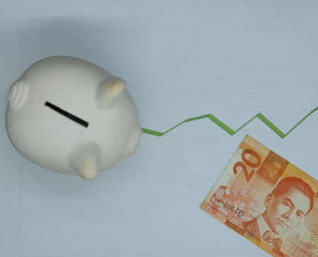 philippine banknote and piggy bank on background with rising trend green line, view from above Foto de archivo