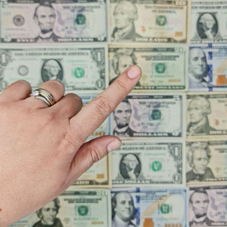 approach to hand of a woman and background with american dollar bills