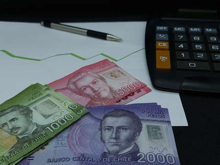 chilean banknotes, pen and calculator on background with rising trend green line