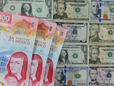 approach to mexican banknotes of 100 pesos and background with american dollar bills Foto de archivo