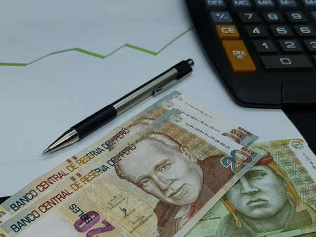 peruvian banknotes, pen and calculator on background with rising trend green line Foto de archivo