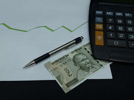 indian banknote, pen and calculator on background with rising trend green line