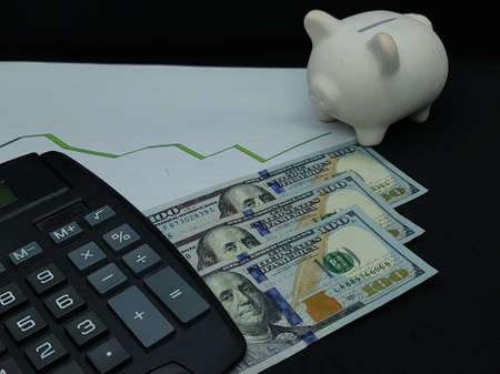 american banknotes of 100 dollars, piggy bank and calculator on background with rising trend green line Foto de archivo