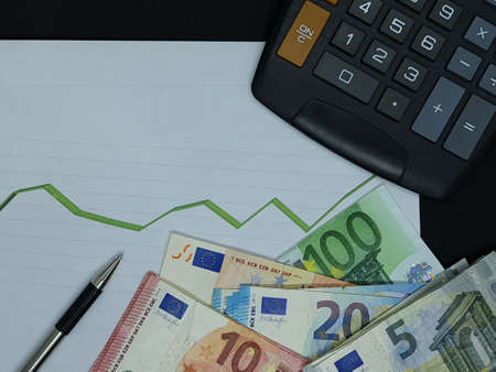 european banknotes, pen and calculator on background with rising trend green line, view from above