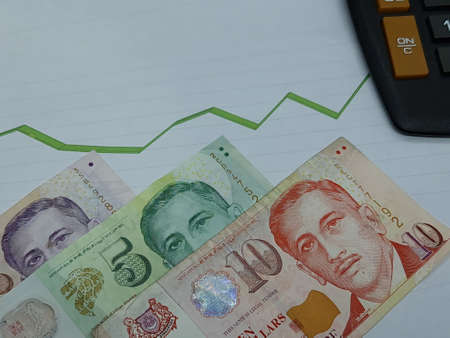 singaporean banknotes and calculator on background with rising trend green line Foto de archivo