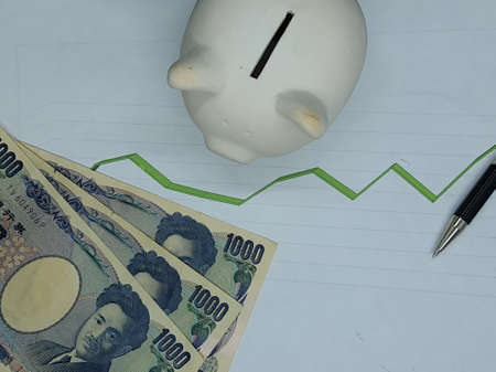 japanese banknotes, pen and piggy bank on background with rising trend green line, view from above