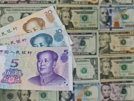 approach to chinese banknotes and background with american dollar bills Foto de archivo