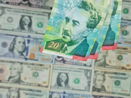 approach to israeli banknotes and background with american dollar bills