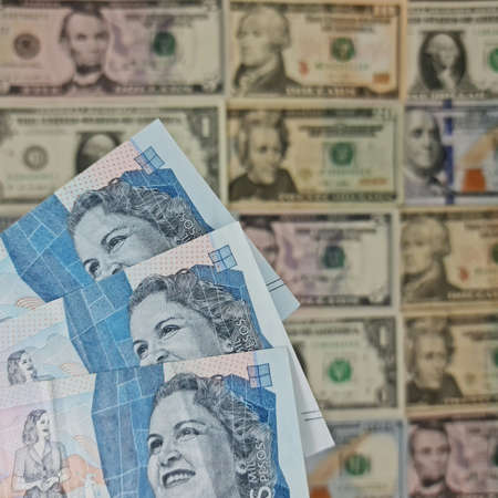 approach to colombian banknotes of 2000 pesos and background with american dollar bills
