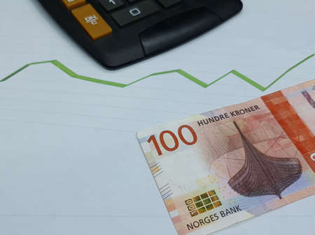 norwegian banknote and calculator on background with rising trend green line