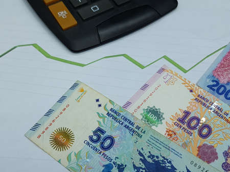 argentine banknotes and calculator on background with rising trend green line