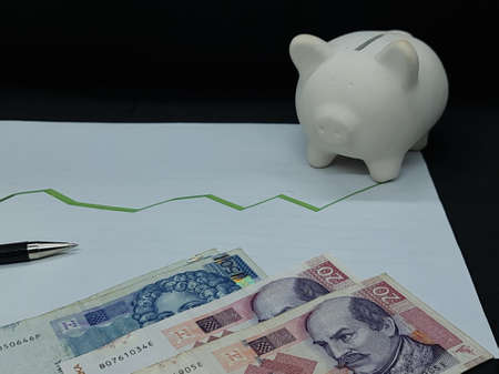 croatian banknotes, pen and piggy bank on background with rising trend green line