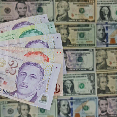 approach to singaporean banknotes and background with american dollar bills