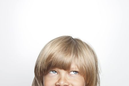 mischevious: Young boy looking up and mischevious Stock Photo