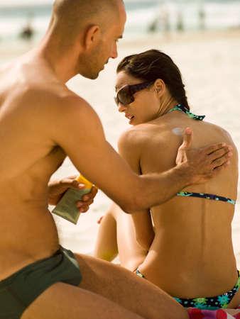 barechested: Man applying suntan lotion on his girlfriend