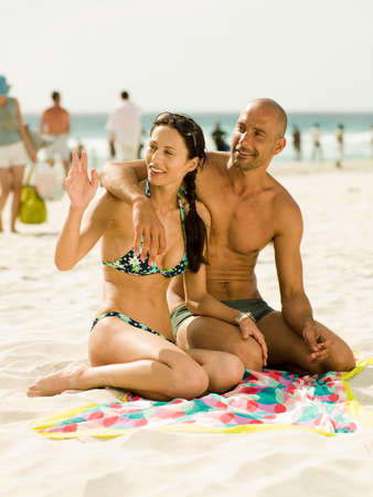 barechested: Couple sitting on the beach