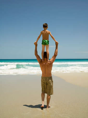 barechested: Father carrying his son on his shoulders