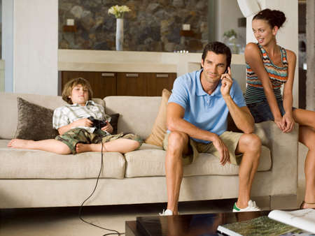 remotes: Boy playing video game,father on the phone