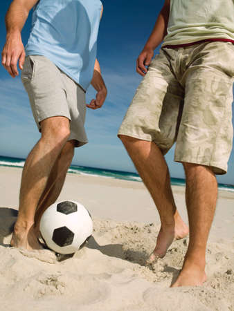lower section: Men playing football on the beach LANG_EVOIMAGES