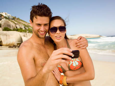 barechested: Couple taking pictures on the beach