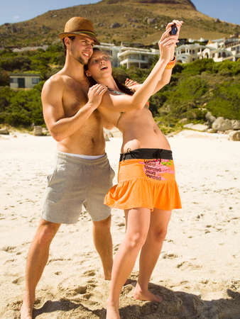 barechested: Couple taking their pictures on the beach