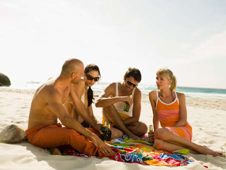 barechested: Friends drinking beer on the beach LANG_EVOIMAGES