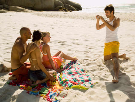 barechested: Man photographing his friends on the beach