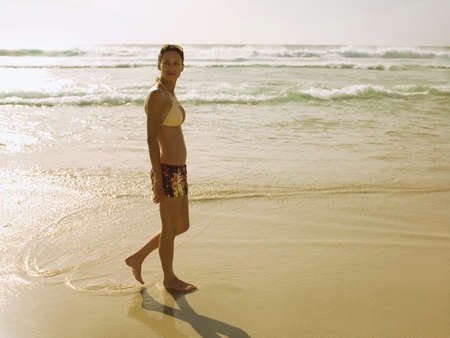 two piece swimsuit: A woman walking on the beach LANG_EVOIMAGES