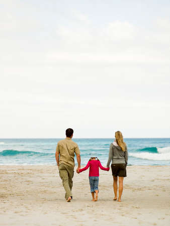 unwinding: Parents walking on the beach with their daughter