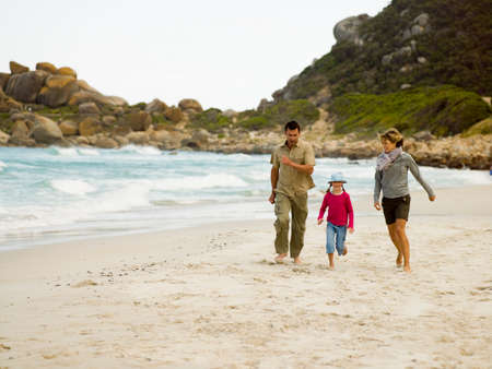 unwinding: Parents running on the beach with their daughter
