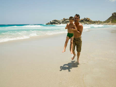 barechested: Father carrying his son and running on the beach