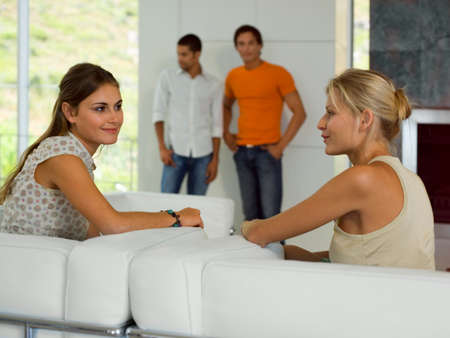 tanktop: Women talking on the sofa, Men standing in the background.