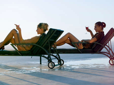 deck chairs: Women relaxing on deck chairs LANG_EVOIMAGES