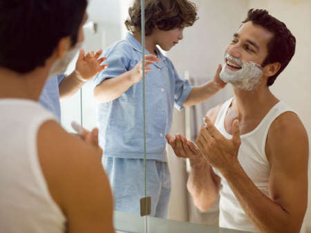son's: Boy applying shaving foam on his father LANG_EVOIMAGES