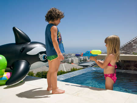 two piece swimsuits: Girl squirting water on her brother