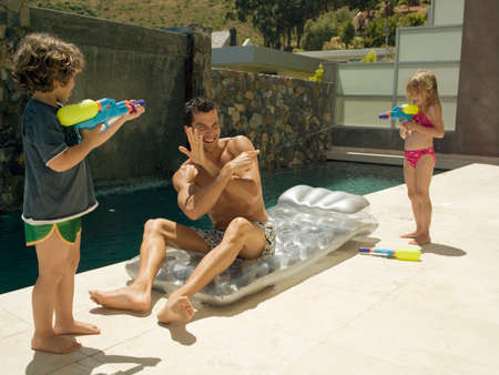 two piece swimsuits: Children squirting water on their father