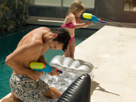 two piece swimsuits: Father and daughter playing with squirt guns